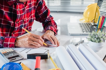 Business man interior designer working and drawing with blueprint and architectural projec
