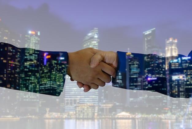Деловое рукопожатие инвестора с городским фоном, цифровыми технологиями, общением, совместной работой, концепцией партнерства