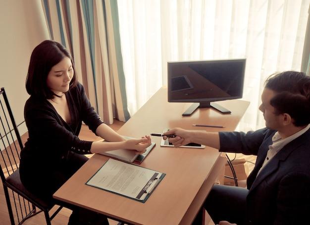Деловой человек передает перо женщине для подписания контракта