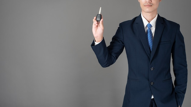 Business man is holding car key