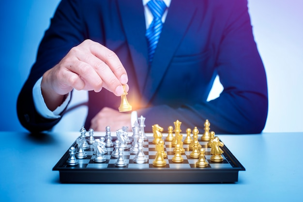Business man is playing chess, business management strategy concept