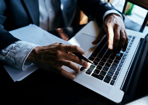 ビジネスマンのラップトップは、ハンドオフィスでペンを文書化します