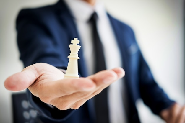 Business man leader of a successful business holding the chess in hand digital composite of chess pieces.
