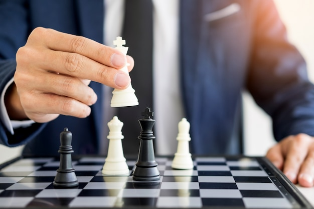 Business man leader of a successful business holding the chess in hand digital composite of chess pieces