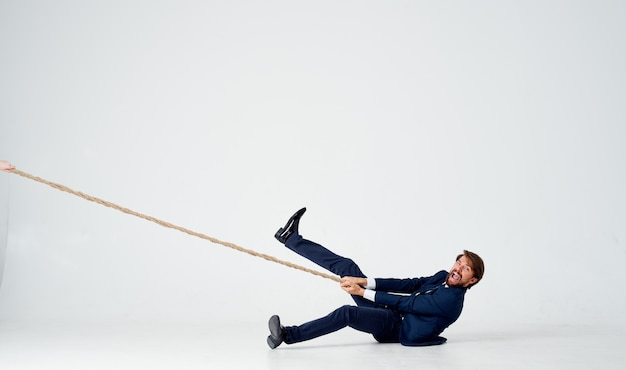 A business man lies on the floor and pulls a rope on a light space indoors