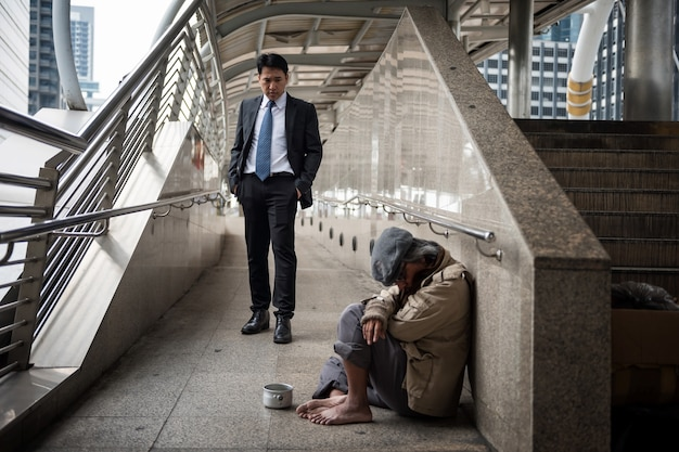 Business man look at homeless in city