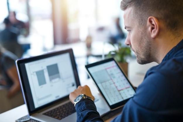 彼のラップトップコンピューターとタブレットでプロジェクトを探して分析するビジネスマン