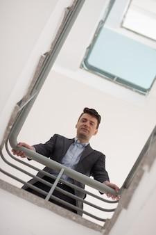L'uomo d'affari guardando dall'alto tromba delle scale