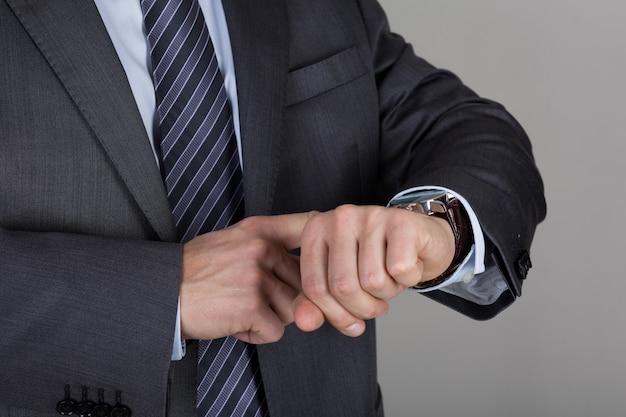ビジネスマンは時間をチェックしている彼の腕時計を見ます。時間管理と期限の概念