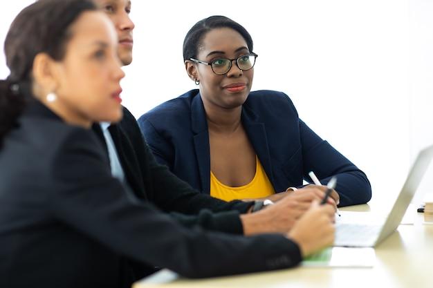 Руководитель менеджера деловой человек на встрече с двумя женщинами, анализирующими ducuments на портативном компьютере в домашнем офисе.