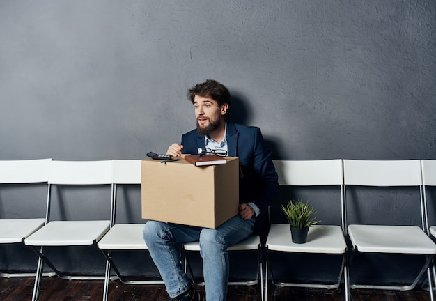 Business man manager sitting on a chair with a box of things dismissal emotions