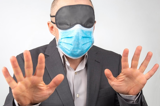Business man in a medical mask and blindfold for sleeping with hands up on a white