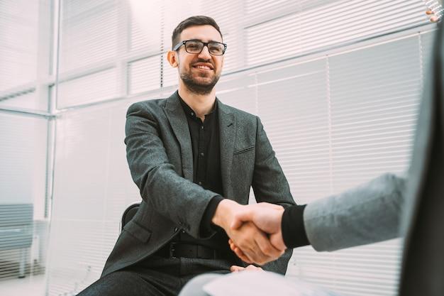 オフィスロビーで彼のビジネスパートナーに会うビジネスマン。テキスト用のスペースのある写真