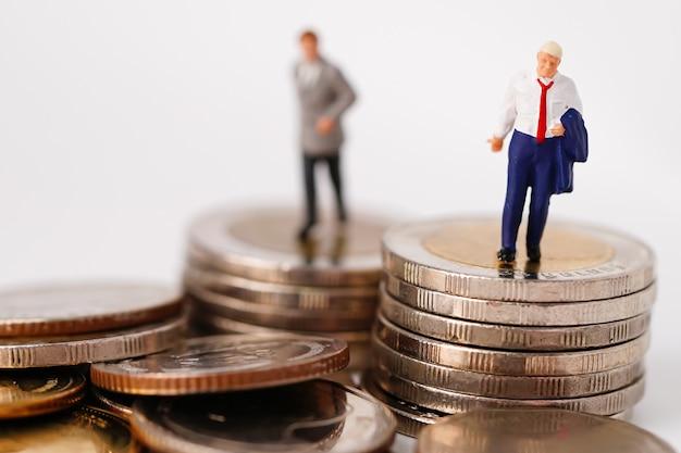 비즈니스 남자 미니어처 사람들이 동전에 서.