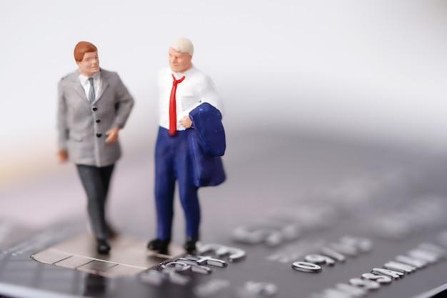 Деловой человек миниатюрные люди стоят на кредитной карте.