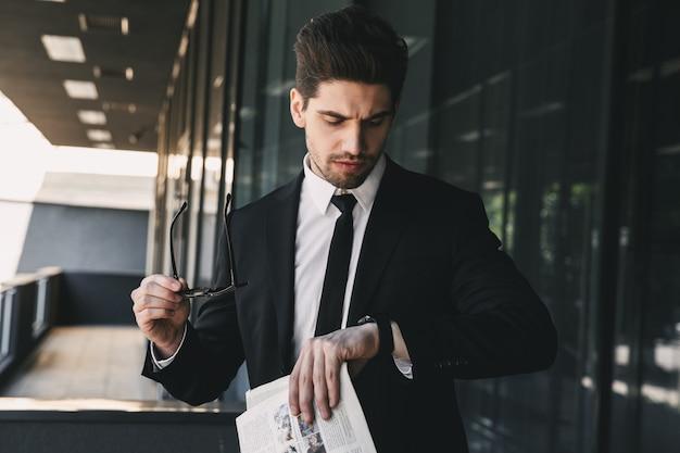 時計を見て新聞を持って探しているビジネスセンターの近くのビジネスマン。