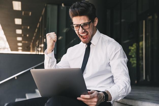 Деловой человек возле бизнес-центра с помощью портативного компьютера делает жест победителя.