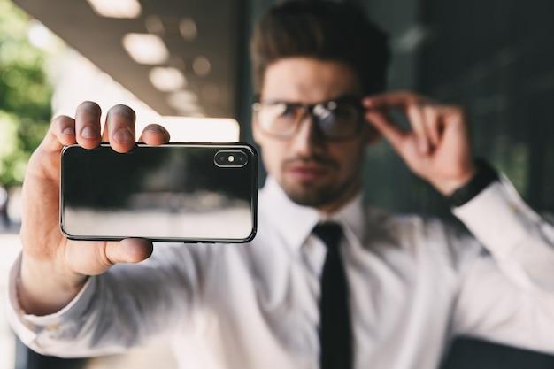携帯電話を使用してビジネスセンターの近くのビジネスマンは自分撮りを取ります。