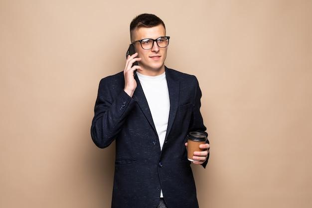Uomo d'affari che negozia sul telefono, isolato su beige