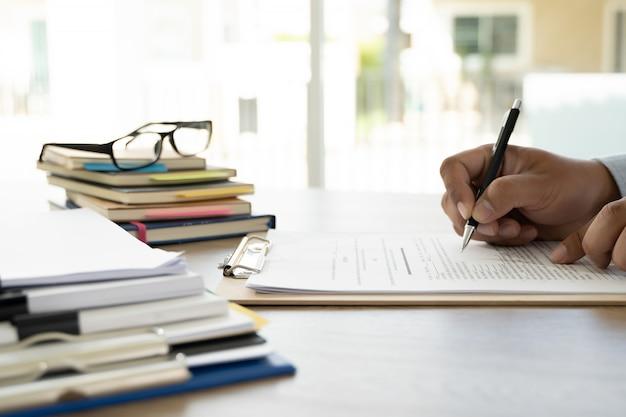 ビジネスの男性ドキュメントとの従業員の労働契約ファイルのスタック紙と法律