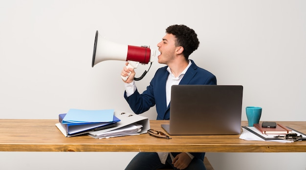Business man in a office shouting through a megaphone
