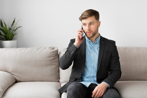 電話で話しているソファの上のビジネスの男性