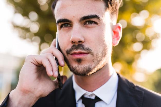 Деловой человек по телефону в парке