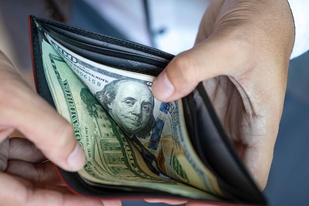 Деловой человек открыть кошелек, чтобы увидеть доллар банкноты