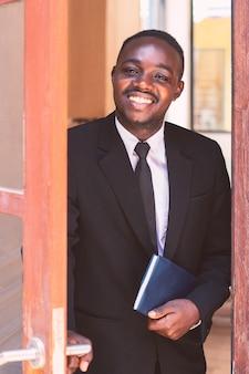 Деловой человек открыл дверь с улыбкой и дружелюбно
