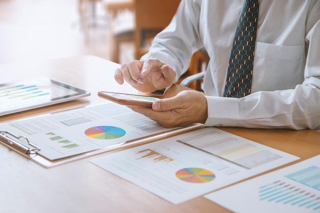 Деловой человек или аналитик в современном офисе, касаясь смартфона, просматривая финансовую отчетность о результатах деятельности или окупаемости инвестиций