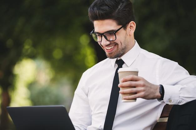 Деловой человек на открытом воздухе в парке, используя портативный компьютер, пить кофе.