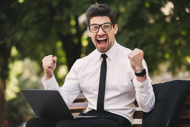 Деловой человек на открытом воздухе в парке с помощью портативного компьютера делает жест победителя.
