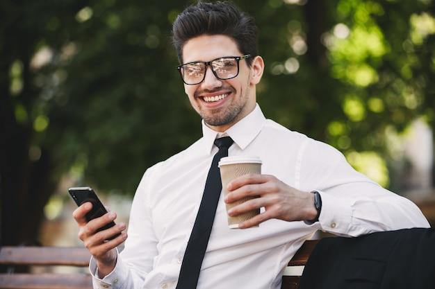 Деловой человек на открытом воздухе в парке, используя кофе мобильного телефона.