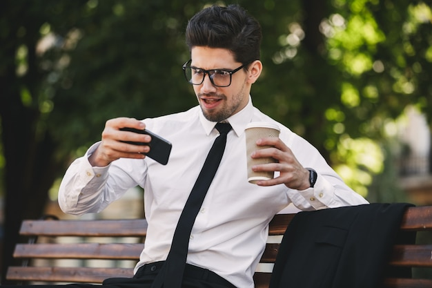 Business man outdoors in the park play games by phone drinking coffee.