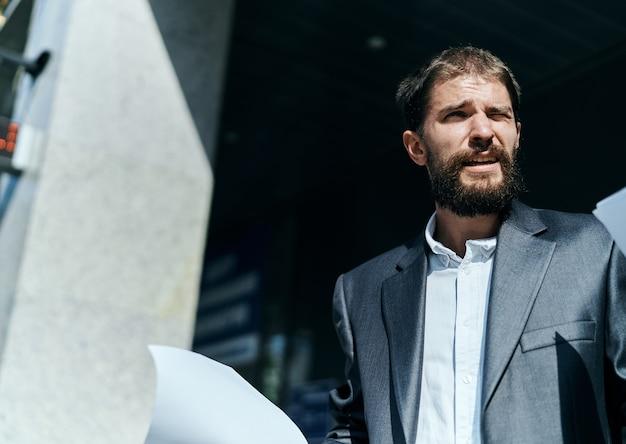 公式のライフスタイルを構築する近くの手にドキュメントを屋外でビジネスの男性。高品質の写真