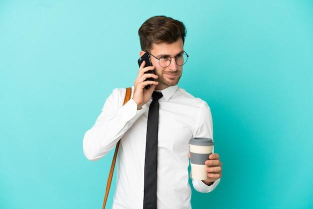 持ち帰り用のコーヒーと携帯電話を保持している孤立した背景上のビジネスマン