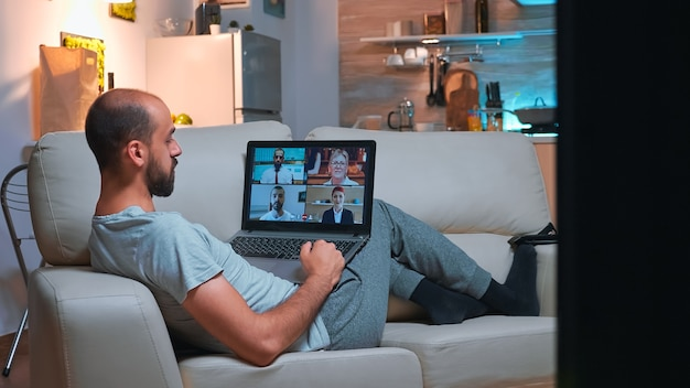 Business man in pajams lying on sofa while chatting with friends