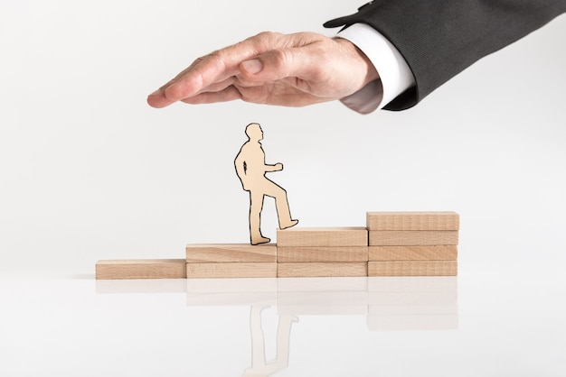 Бумажный вырез делового человека, поднимающийся по ступеням к успеху из сложенных деревянных блоков.