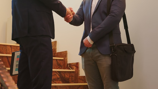 ビジネスマンのパートナーの幹部が話しながらオフィスビルの階段で握手します。現代の金融職場で一緒に働くスーツを着たプロの成功したビジネスマンのグループ。
