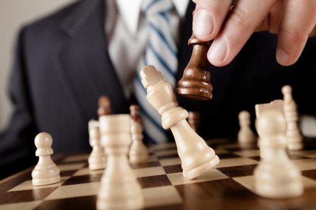Деловой человек играет в шахматы - мат. шахматные фигуры крупным планом