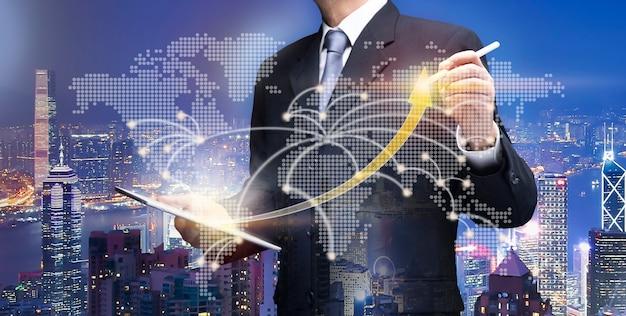 矢印グラフ上のビジネスマンのポイント。都市のビジネスマンは、ipadタブレットを使用して、世界地図に高レートのチャートを描画します金融ビジネス、ビジネス利益計画、株式市場への投資、世界経済の概念