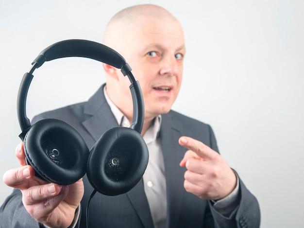 흰색 배경에서 음악을 듣기 위해 헤드폰에서 가리키는 사업가