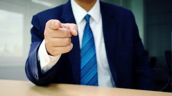 Business man pointing finger at you at desk