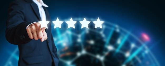 Business man pointing five star icon to give rate of company customer service on blur city night background