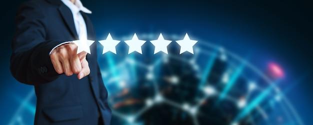 Деловой человек, указывающий значок с пятью звездочками, чтобы дать оценку обслуживания клиентов компании на размытом ночном фоне города