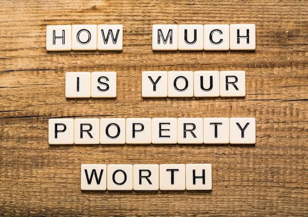 テキストで透明なボードを指しているビジネスマン:あなたの財産の価値はいくらですか?