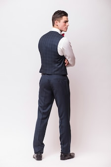 Business man posing backwards, isolated over white wall