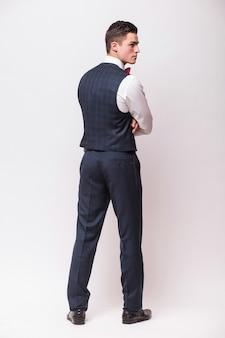 Uomo d'affari in posa all'indietro, isolato sopra il muro bianco