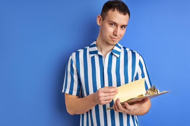 Деловой человек позирует с буфером обмена с бумагами, читая заметки, в синей полосатой рубашке