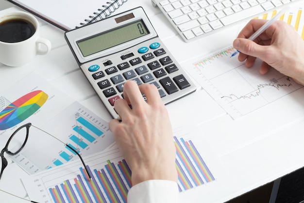 Business man prepares a financial report working with a calculator.